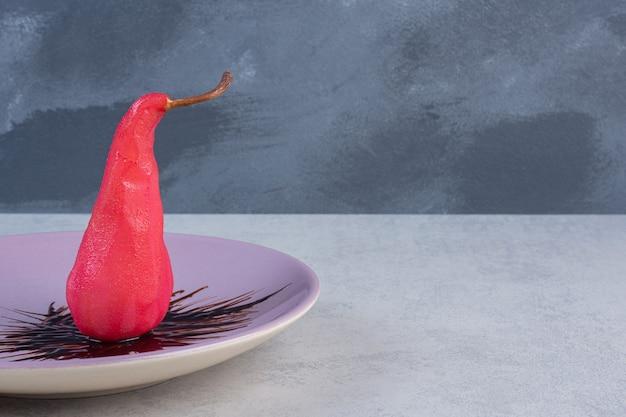 Frische rote birne mit schokolade auf violettem teller.
