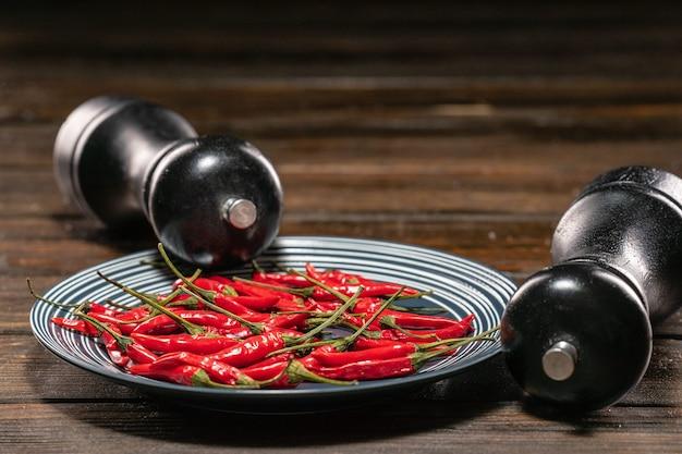 Frische rote chilischoten in einem teller auf einem holztisch mit einem black salt und pepper grinder set