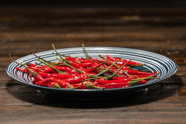 Frische rote chilischoten in einem teller auf einem holztisch Premium Fotos