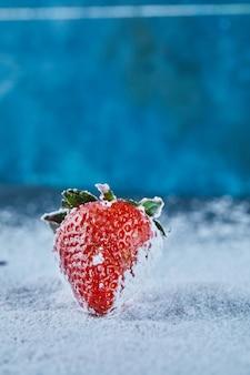 Frische rote erdbeere auf blauer oberfläche mit pulver