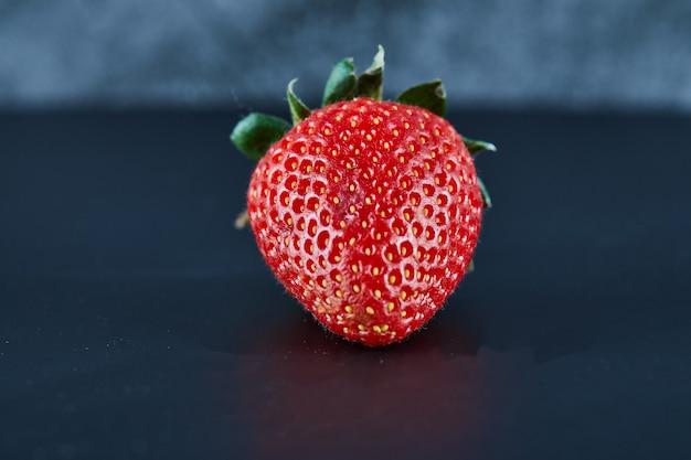 Frische rote erdbeere auf dunkler oberfläche. nahansicht