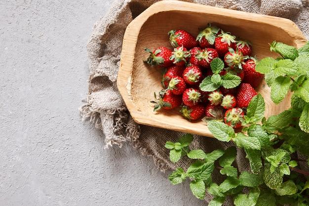 Frische rote erdbeeren auf holzplatte