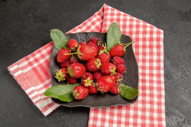 Frische rote erdbeeren der halben draufsicht innerhalb der platte auf dunkler reifer beere der dunklen tischfarbe
