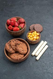 Frische rote erdbeeren der halben draufsicht mit süßen keksen auf dunklem tischzuckerplätzchenkuchen