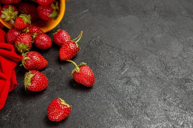 Frische rote erdbeeren der vorderansicht auf dem dunklen hintergrund