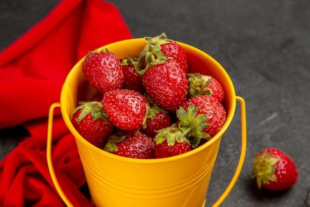 Frische rote erdbeeren der vorderansicht innerhalb des kleinen korbs auf dem dunklen hintergrund