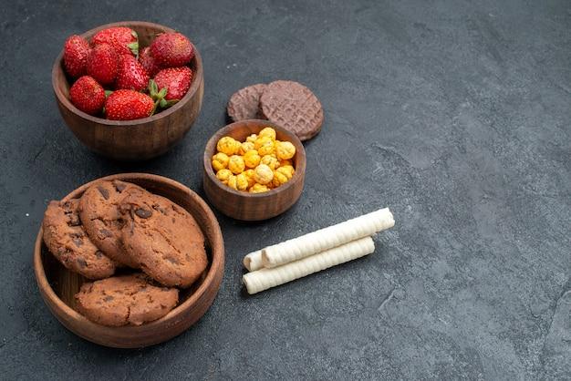 Frische rote erdbeeren der vorderansicht mit süßen keksen auf dunklem hintergrund
