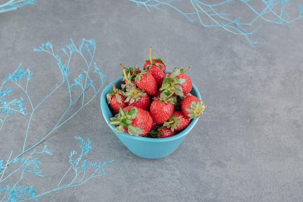 Frische rote erdbeeren in blauer schüssel. foto in hoher qualität