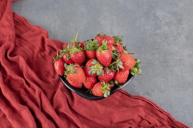 Frische rote erdbeeren in schwarzer schüssel. foto in hoher qualität