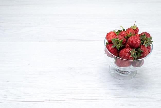 Frische rote erdbeeren in transparentem teller auf hellweiß