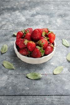 Frische rote erdbeeren in weißer platte zusammen mit grünen getrockneten blättern auf grau