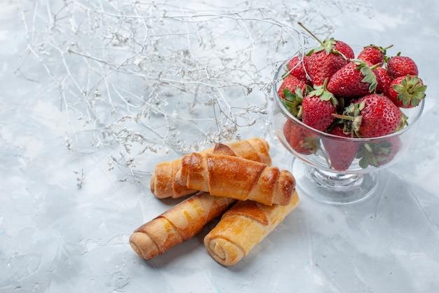 Frische rote erdbeeren milde sommerbeeren in glasplatte mit süßen armreifen auf hellem schreibtisch