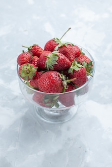 Frische rote erdbeeren milde sommerbeeren innerhalb der glasplatte auf weißem schreibtisch