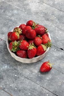 Frische rote erdbeeren milde und reife früchte innerhalb platte auf grauem schreibtisch