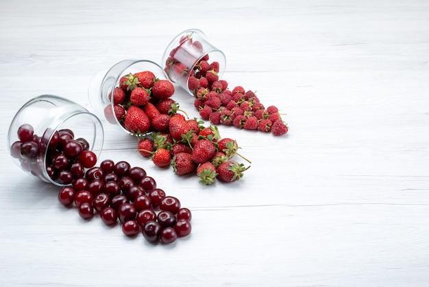 Frische rote erdbeeren mit sauren frischen kirschen und himbeeren auf licht