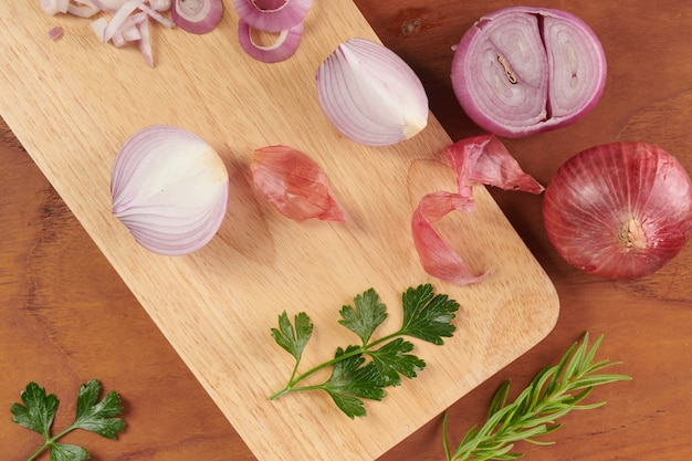 Frische rote ganze und geschnittene zwiebel. geschnittene rote zwiebel mit petersilie und rosmarin. zwiebel und scheiben auf holzschneidebrett. frisch gepflückt aus heimischem bio-garten. lebensmittelkonzept.