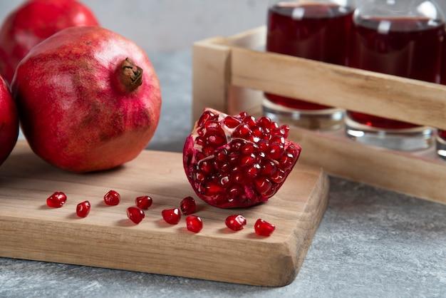 Frische rote granatäpfel auf holzbrett mit saft.