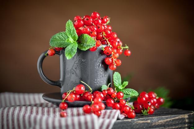 Frische rote johannisbeeren in einer tasse auf einem dunklen rustikalen holztisch.