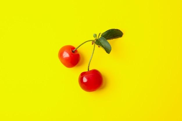 Frische rote kirsche auf gelbem raum, nahaufnahme