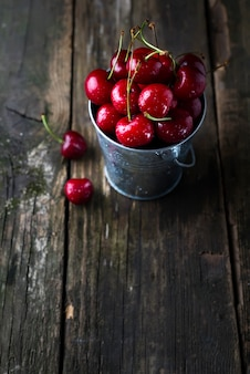 Frische rote kirschen auf holztisch mit wassertropfen