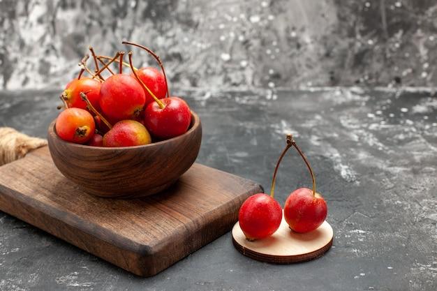 Frische rote kirschen in einer braunen schüssel auf einem kleinen schneidebrett