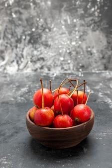 Frische rote kirschfrucht in einer schüssel auf grauem hintergrund