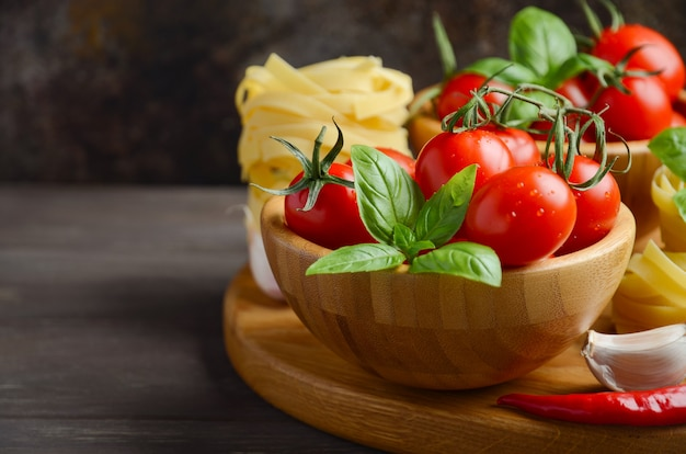 Frische rote kirschtomaten mit rohen teigwaren, basilikum, paprikapfeffer und knoblauch für italienisches lebensmittel.