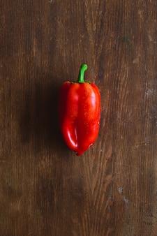 Frische rote paprika auf hölzernen hintergrund