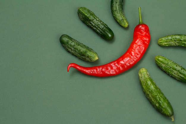 Frische rote paprika und gurken auf grünem hintergrund. ansicht von oben.