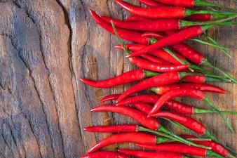 Frische rote Paprikas auf einem hölzernen Hintergrund