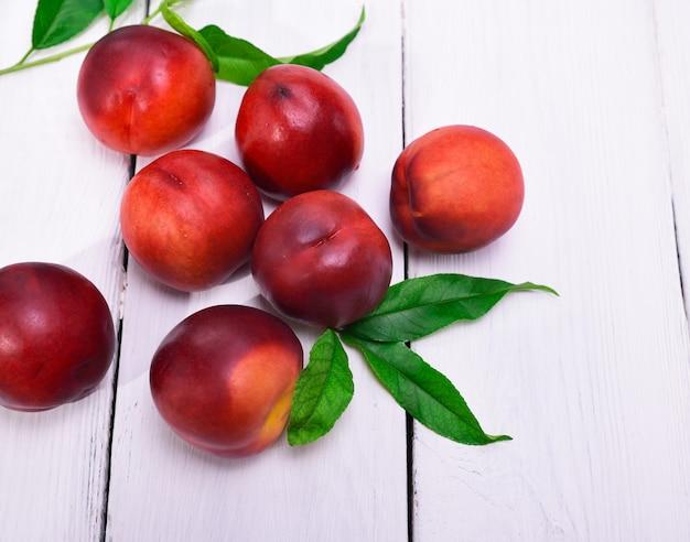 Frische rote pfirsiche auf einem weißen hölzernen hintergrund