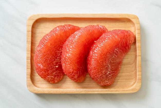Frische rote pomelo-frucht oder grapefruit auf teller