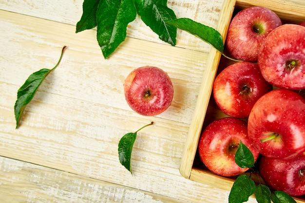 Frische rote reife apfelfrüchte in der holzkiste