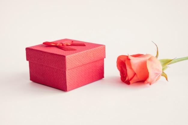 Frische rote rosen und rote bogengeschenkbox auf weißem hintergrund