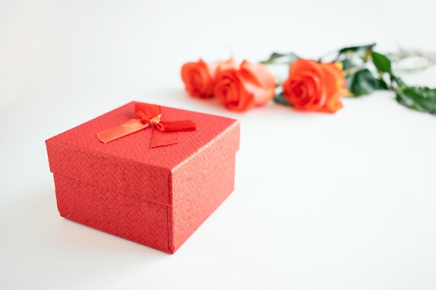 Frische rote rosen und rote bogengeschenkbox