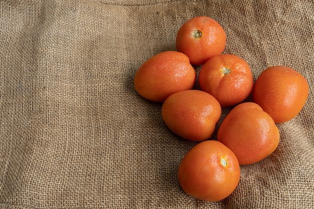 Frische rote tomaten auf einer jutefasermatte