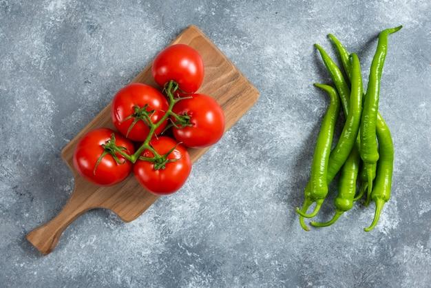 Frische rote tomaten auf holzbrett mit chilischoten.