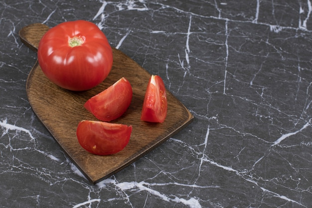 Frische rote tomaten auf holzbrett.