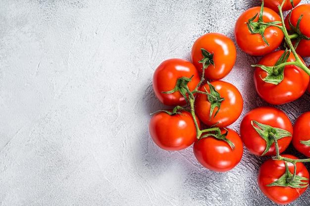 Frische rote tomaten auf küchentisch. weißer hintergrund. draufsicht. speicherplatz kopieren.
