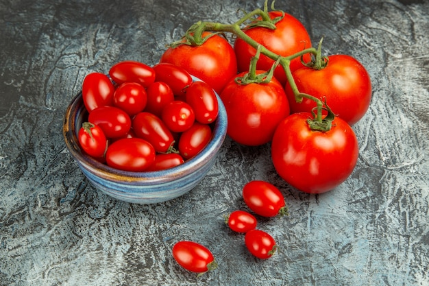 Frische rote tomaten der vorderansicht auf einem dunklen hellen hintergrund