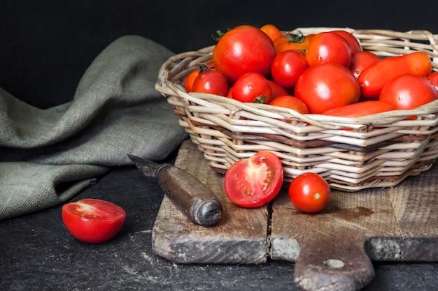 Frische rote tomaten im weidenkorb auf schwarzem hintergrund.