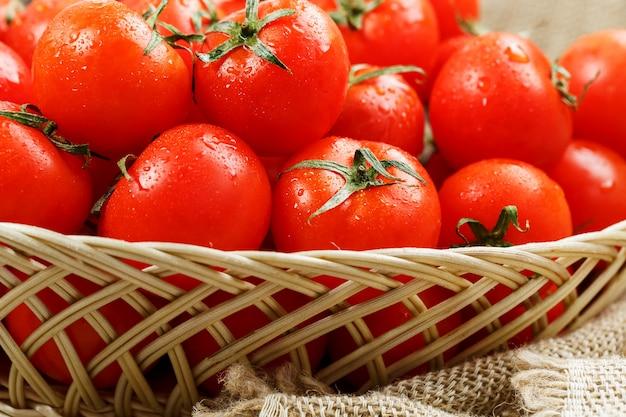 Frische rote tomaten in einem weidenkorb auf einem alten holztisch. reife und saftige kirschtomaten mit feuchtigkeitstropfen, grauer holztisch, um einen stoff aus sackleinen. im rustikalen stil.