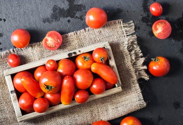 Frische rote tomaten in holzkiste auf schwarzem hintergrund. flache lage, ansicht von oben