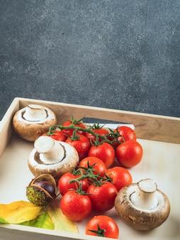 Frische rote tomaten; pilze und kastanien in holztablett