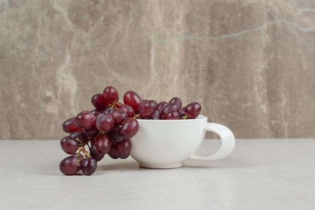 Frische rote trauben in weißer tasse