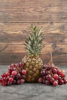 Frische rote trauben mit reifer ananas auf marmoroberfläche.
