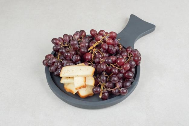 Frische rote trauben und käsescheiben auf dunklem brett.