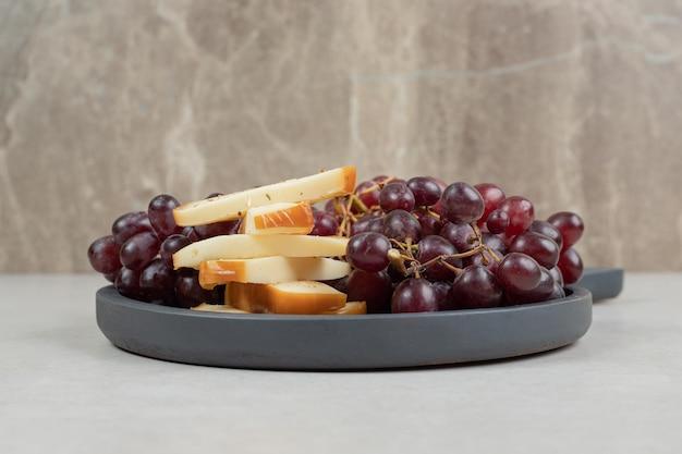 Frische rote trauben und käsescheiben auf dunklem brett