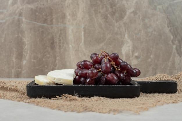Frische rote trauben und weißer käse auf schwarzem brett