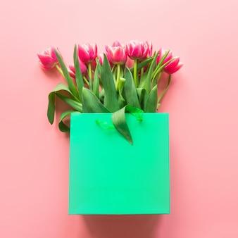 Frische rote tulpe blüht in der grünen papiertüte auf rosa. frühling.